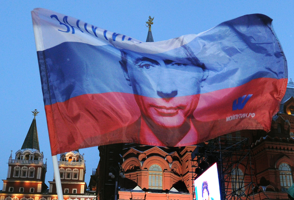 A Russian flag featuring Prime Minister Vladimir Putin flies above his supporters as they celebrate Putin's victory as they rally at the central Manezhnaya Square just outside the Kremlin in Moscow, March 5, 2012.