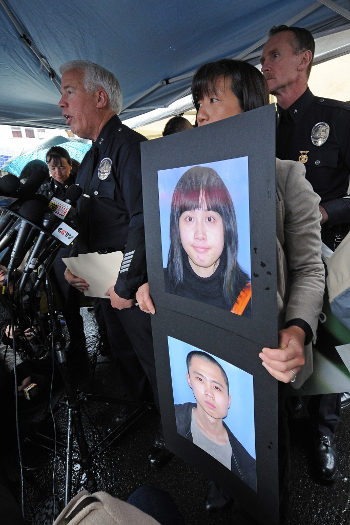 Los Angeles Police Department Officer Suzan Nelson holds photos of Chinese foreign exchange students Ming Qu (bottom) and Ying Wu (top) at a press conference to announce a USD $125,000 reward for information leading to an arrest in the murder of the two University of Southern California (USC) students from China, during a news conference April 13, 2012 in the Los Angeles street where the murders occured two days ago.  AFP PHOTO / Robyn Beck (Photo credit should read ROBYN BECK/AFP/Getty Images)