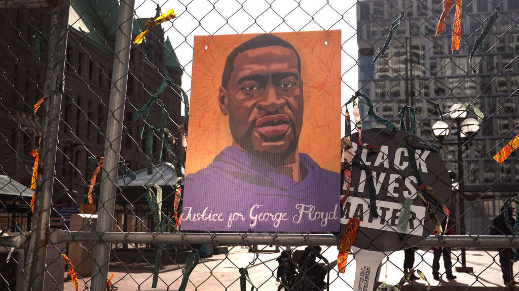 A picture of George Floyd hangs on a fence barrier that surrounds the Hennepin County Government Center in Minneapolis on March 30. The Justice Department is bringing criminal charges against former police officer Derek Chauvin over allegedly violating Floyd's rights and using excessive force in restraining him.