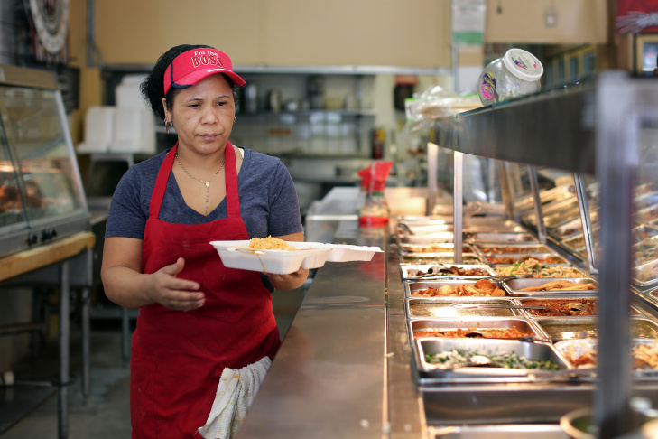 Enedina Arrellano, a cook at Ponci Burrito Express in Altadena, makes a to-go order for a customer on Thursday, March 27. The store first opened in 1992 as a convenience store with a meat counter and was called Nuevo Poncitlan Meat Market.
