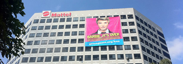Greenpeace protesters hang a banner of Ken protesting Mattel's actions in the Indonesian rainforest at a Mattel office building.
