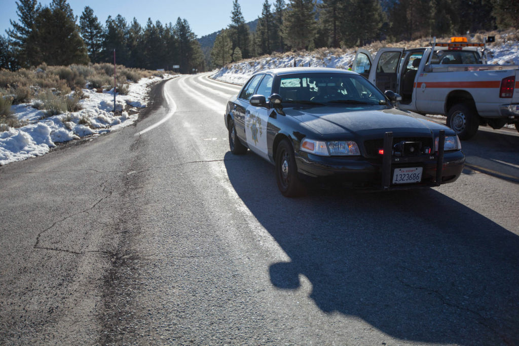 California Highway Patrol officers block off Highway 38 at Angelus Oaks; beyond the block is where police confronted Christopher Dorner and chased him to a cabin.