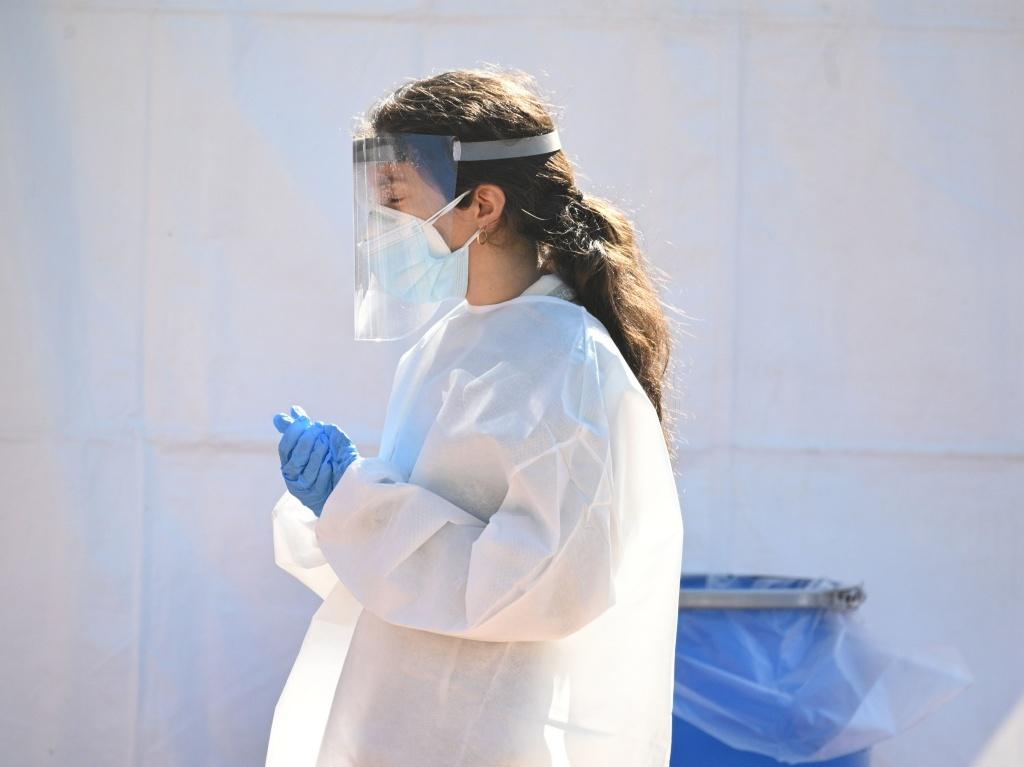 A health care worker is seen at a walk-up coronavirus testing site this week in San Fernando, Calif.