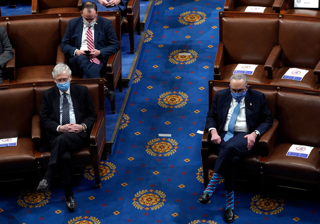 U.S. Senate Majority Leader Mitch McConnell (L) (R-KY) looks on with U.S. Senate Minority Leader Chuck Schumer (L) (in the House Chamber during a reconvening of a joint session of Congress on January 06, 2021 in Washington, DC.