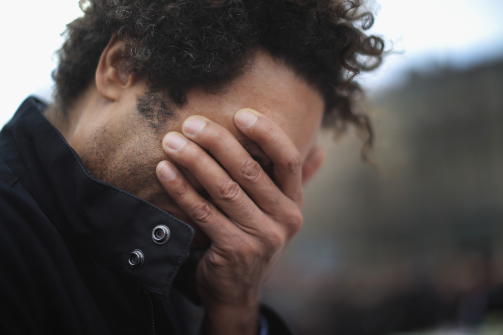 A man weeps for a lost friend as people gather to observe a minute-silence at the Place de la Republique in memory of the victims of the Paris terror attacks last Friday, on November 16, 2015.