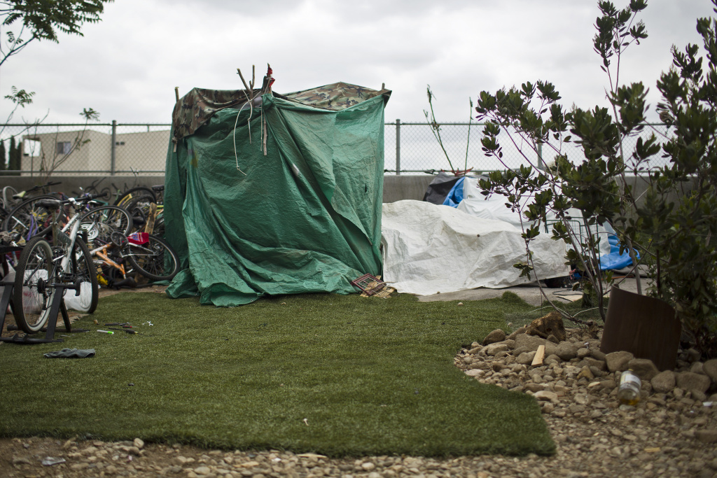 Pieces of artificial turf and rugs surround a tent in the Arroyo Seco riverbed along the 110 Freeway on Tuesday morning, May 5, 2015.