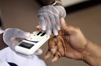 A man's finger is pricked to test his cholesterol at the City of Newark's free homeless health fair at the Department of Child and Family Well-Being on August 13, 2009 in Newark, New Jersey.