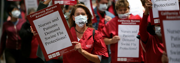 Nurses and hospital workers carry signs and wear masks as they protest outside of the University of California San Francisco medical center August 5, 2009 in San Francisco, California.