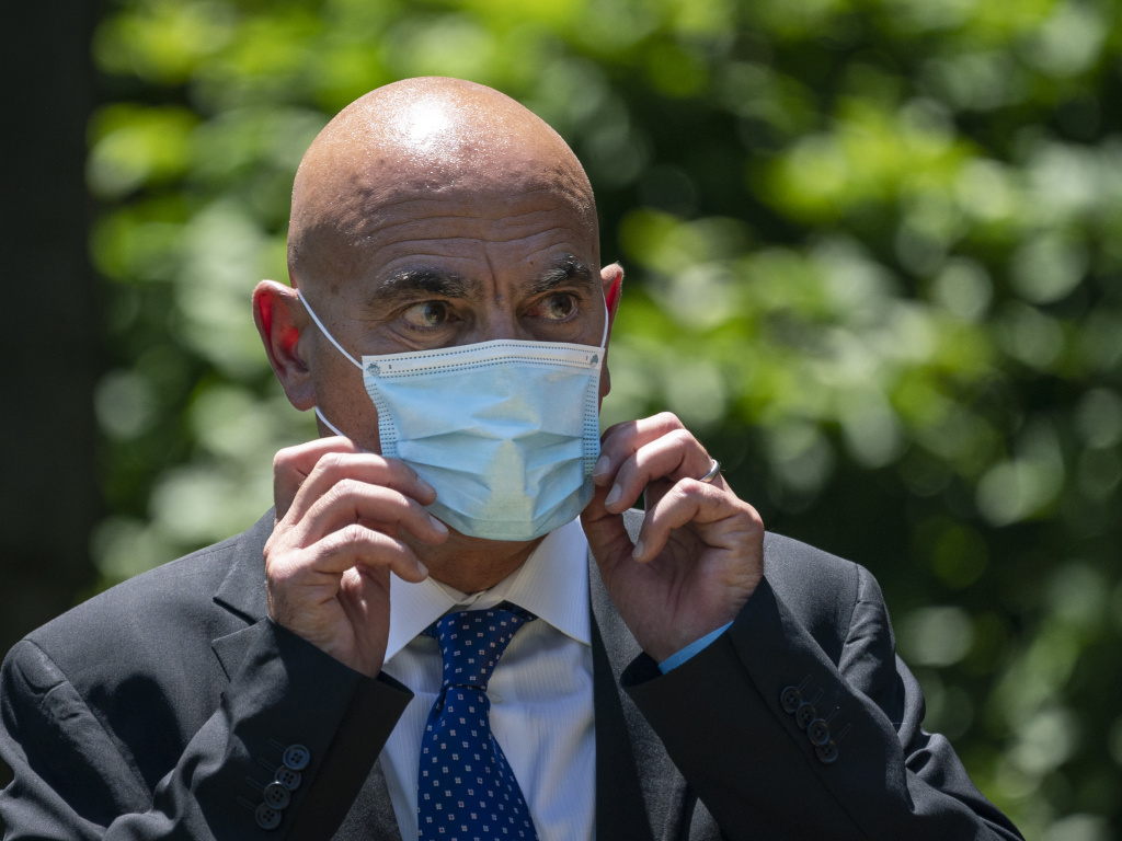Dr. Moncef Slaoui, chief scientific adviser for Operation Warp Speed, listens as President Trump delivers remarks about coronavirus vaccine development in the Rose Garden on May 15. Slaoui says Americans could start seeing a vaccine by the middle of December.
