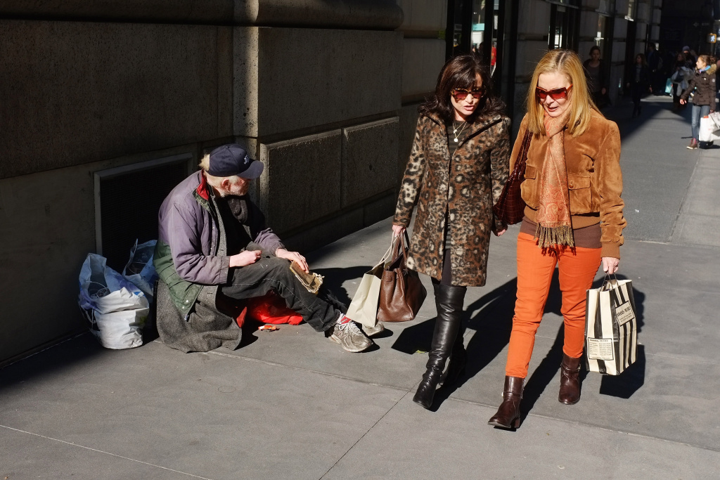 In New York City, Women walk by a panhandler along Madison Avenue.