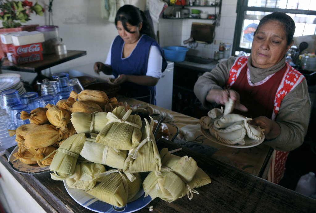 Tamales are displayed in a bar as women prepare empanadas in Salta, at the foothills of the Andes mountain range, in the Argentine northern province of Salta, on June 14, 2009.
