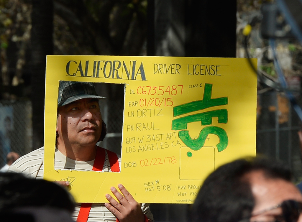 In this file photo, Raul Ortega holds a sign as he celebrates after California Governor Jerry Brown signed bill AB60 on the steps of Los Angeles City Hall in October 2013. The law, which went into effect in 2015, allows people in the country illegally to receive a permit to drive in the state. A new study from Stanford University finds this change may be reducing the number of hit-and-run incidents.