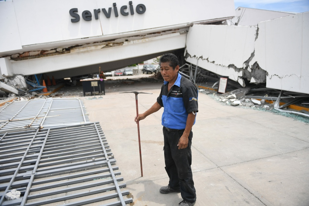 A man stands helpless in front of a building that collapsed in Juchitan de Zaragoza, Oaxaca after an 8.1 earthquake that hit Mexico on September 8, 2017.