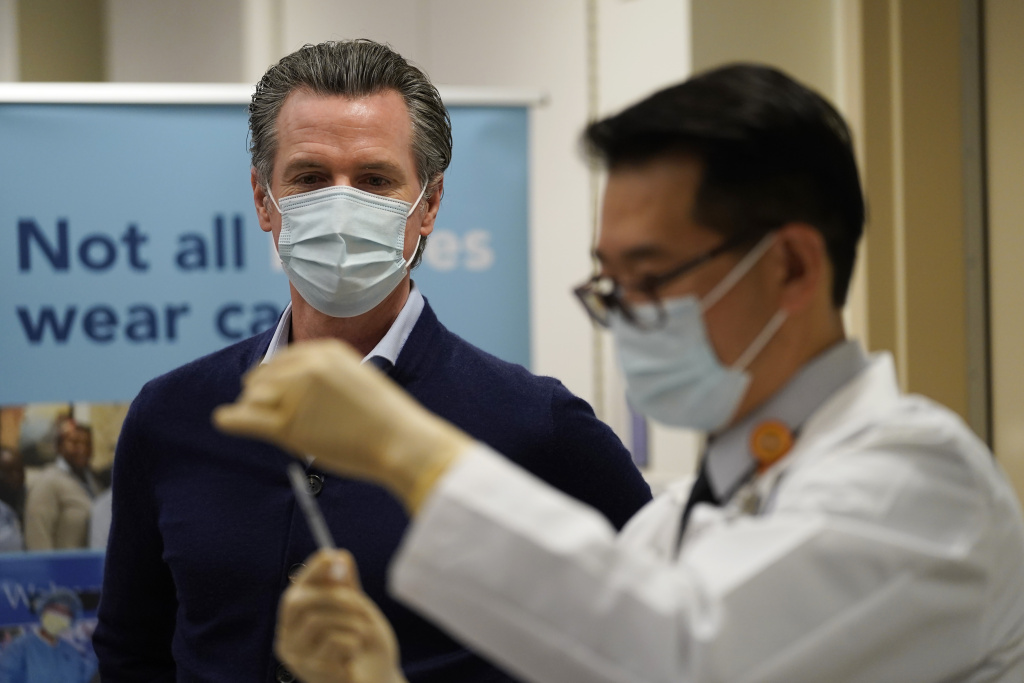 Gov. Gavin Newsom watches as the Pfizer-BioNTech COVID-19 vaccine is prepared by Director of Inpatient Pharmacy David Cheng at Kaiser Permanente Los Angeles Medical Center on December 14, 2020 in Los Angeles, California.