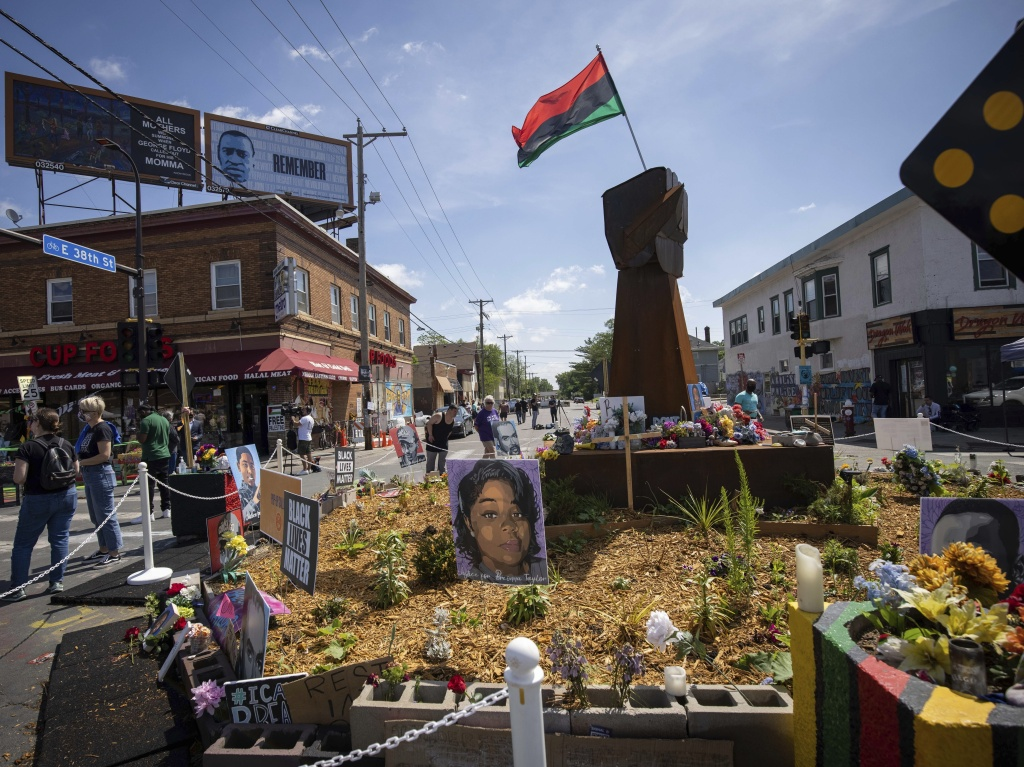 People walk through George Floyd Square after shots were fired on the one year anniversary of Floyd's murder in Minneapolis, Minn. The intersection was disrupted by gunfire just hours before it was to be the site of a family-friendly street festival.