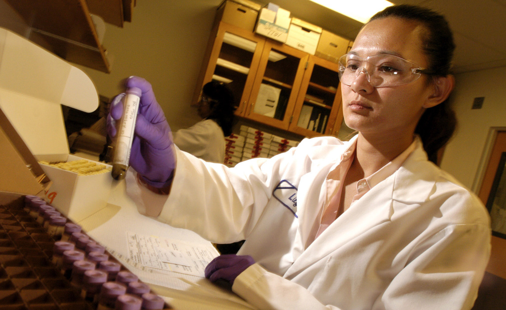 In this file photo, Lily Zimmerman processes blood from a DNA collection kit at California's DNA laboratory in Richmond, Calif., on July 22, 2004. Proposition 69, passed by voters later that year, greatly expanded the collection of DNA samples, not only from convicted criminals but from anyone arrested for an alleged felony starting in 2009.