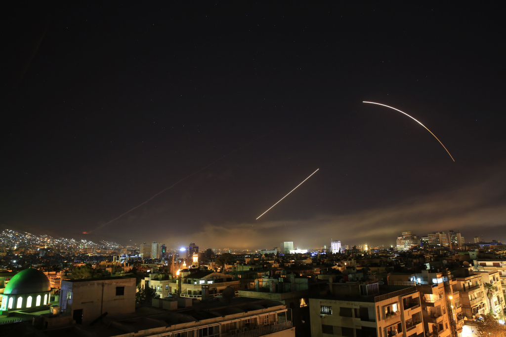 Missiles streak across the Damascus skyline as the U.S. launches an attack on Syria targeting different parts of the capital, early Saturday, April 14, 2018. Syria's capital has been rocked by loud explosions that lit up the sky with heavy smoke as President Donald Trump announced airstrikes in retaliation for the country's alleged use of chemical weapons.