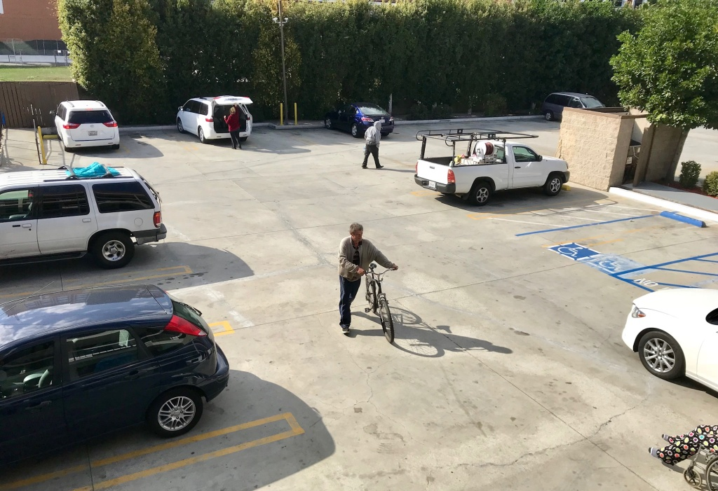 Fritz Reichenbach pushes his bicycle across the parking lot of the Buena Park motel he's staying at.