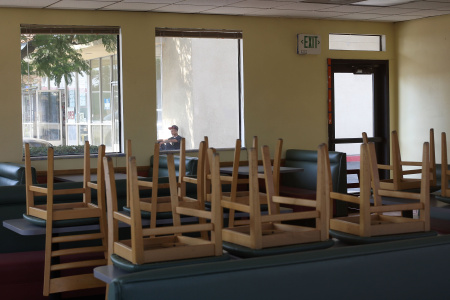 Chairs remain on dining tables inside a drive-through fast food restaurant in a strip mall after its tenants had been evicted on October 8, 2009 in Fontana, California.