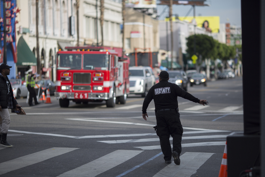 File: A security guard stops pedestrian traffic for an approaching fire truck on Hollywood Boulevard where preparations were being made for the premiere of Walt Disney Pictures And Lucasfilm's