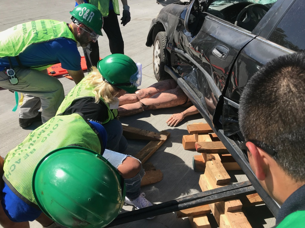CERT trainees use crowbars and wooden blocks to lift a vehicle off of a dummy victim.