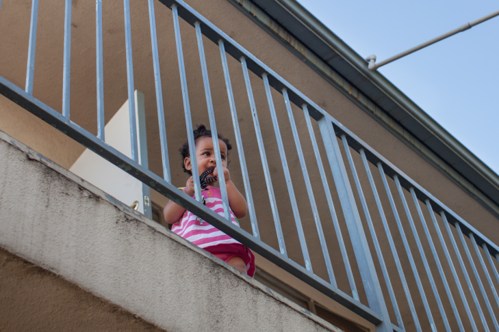 Lola Mae Bray looks out of the second floor of the Community Prisoner Mother Program in Pomona, Calif. where children under age seven live with their incarcerated mothers.