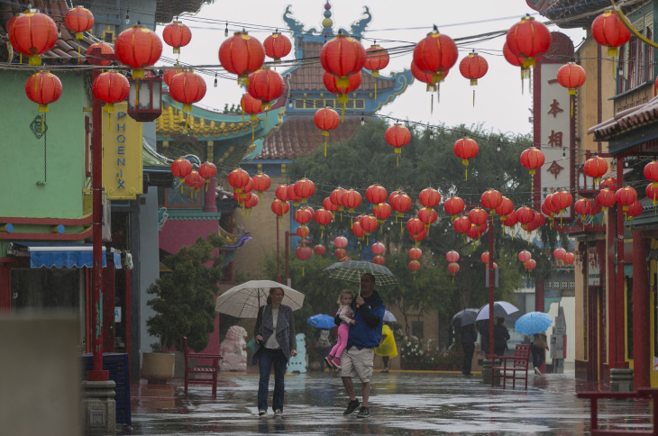 Pedestrians walk under the rain in the Chinatown Plaza in Los Angeles on Friday, April 8, 2016. The first of two weather systems has brought showers to Southern California, but rainfall has been scattered and mostly light. The National Weather Service says radar shows showers running across the region early Friday, but not much of the rain is reaching the ground. (AP Photo/Damian Dovarganes)