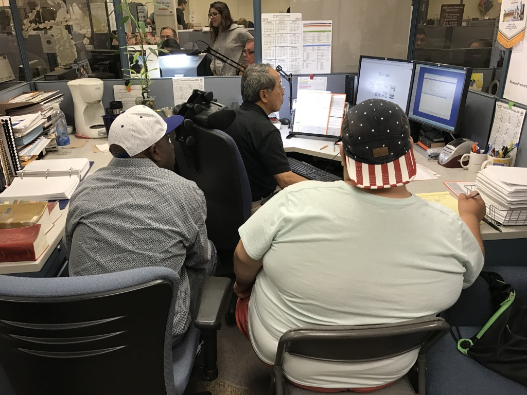 Election observers watch an employee input provisional ballots at the Orange County Registrar of Voters.
