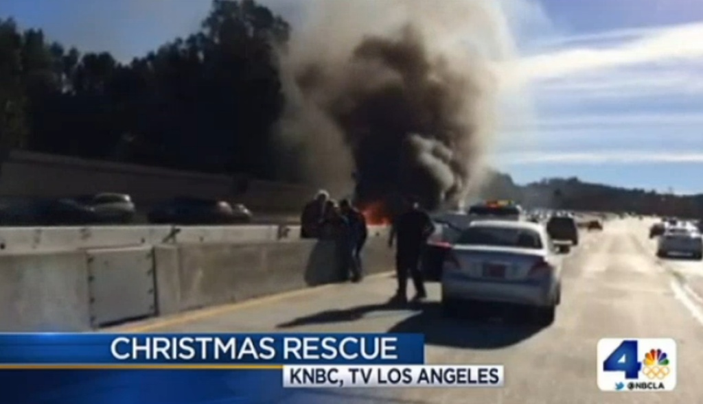 An LAPD officer and good Samaritans rescue a man from a burning car on the 405 freeway on Christmas Day 2013. (Screencap from NBCLA.)