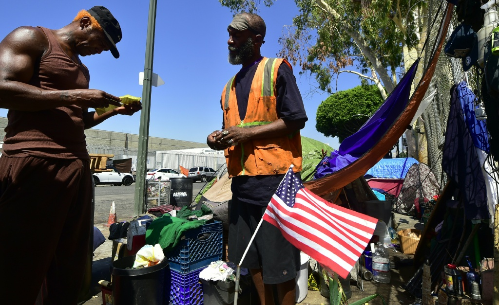 Homeless veteran Kendrick Bailey (C) and General Dogon (L) outside Bailey's tent on a streetcorner near Skid Row in downtown Los Angeles, California on June 20, 2017.