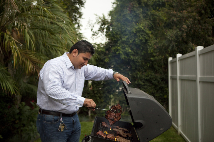 Los Angeles, CA: July 12, 2012 - Ronald Aldana stands near the front door of his home, watching for rain, before relighting the grill where he is in the process of cooking food for dinner for his girlfriend, her mother and friends.