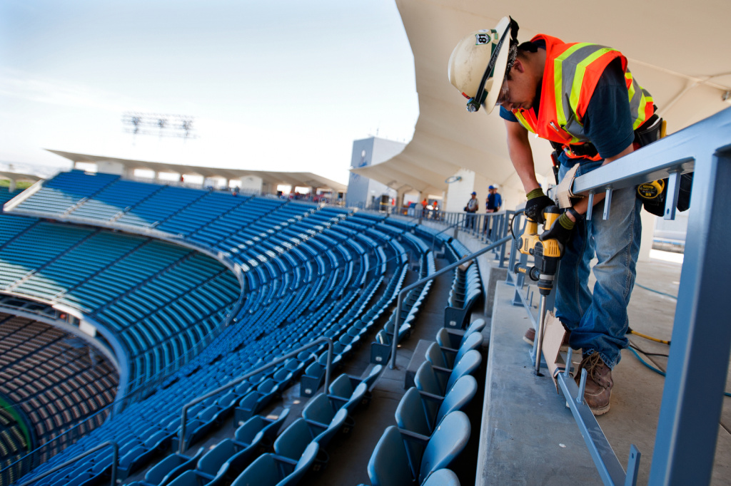 Luis Magdaleno, an electrician for Morrow Meadows, drills holes for wiring in handicap stalls, so that attendees can plug in their electronics. Renovations are taking place at Dodger Stadium before opening day on April 1. Magdaleno has been working on the park for four weeks.