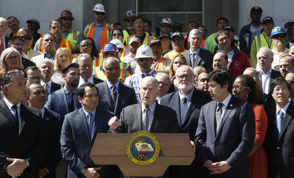 California Gov. Jerry Brown announces a plan to raise $52 billion to fix California roads during a news conference March 29, 2017, in Sacramento. The 10-year plan would boost the gasoline excise tax by 12 cents a gallon along with higher registration fees and a $100 charge on emission-free vehicles. Brown was flanked by Assembly Speaker Anthony Rendon, D-Paramount, third from left, and Senate President Pro Tem Kevin de Leon, D-Los Angeles, third from right, along with other lawmakers, and supporters of the plan.