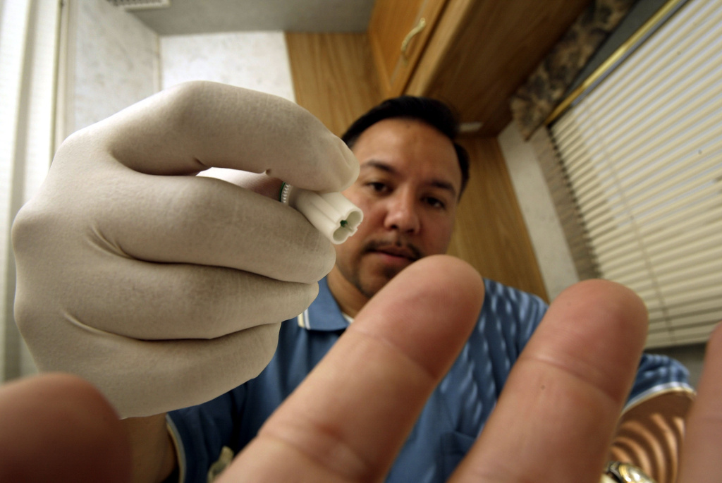 A mobile testing program manager uses a photographer's finger to demonstrate how to obtain a blood sample to test for HIV inside a mobile HIV screening lab in Los Angeles.