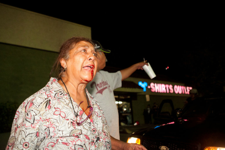 Yolanda Delgado cries out to end the destruction of local properties after violence erupted between police officers and protesters during demonstrations to show outrage for the fatal shooting of Diaz on July 24, 2012.
