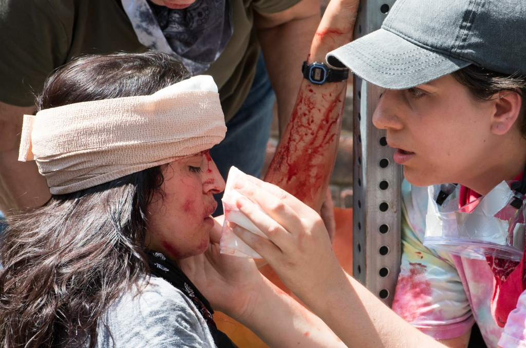 A woman receives first-aid after a car ran into a crowd of counter-protesters in Charlottesville, Virginia on August 12, 2017.
