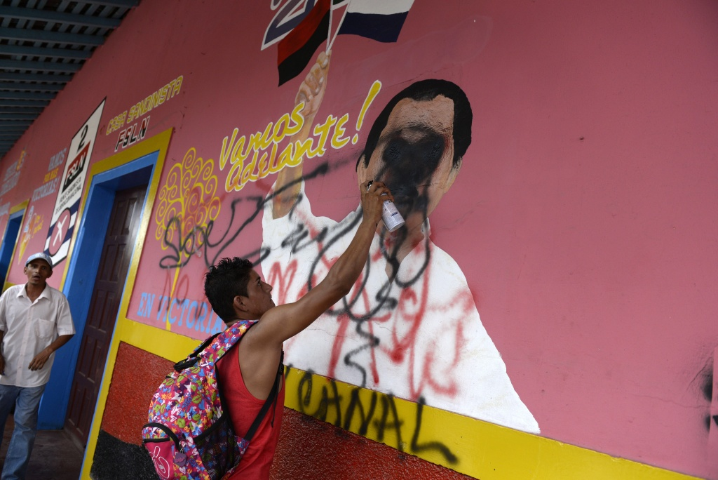 A peasant makes a graffiti on a mural of Nicaraguan Presidnet Daniel Ortega during a protest against the construction of an inter-oceanic canal in Juigalpa, Nicaragua on June 13, 2015. Nicaragua and Chinese company HKND Group last year launched construction of an ambitious $50 billion rival to the Panama canal that could handle even larger ships. The canal, which is set to be completed within five years, threatens to displace a small village of the Rama ethnic group and to invade the Indio Maiz reserve, according to environmentalists.