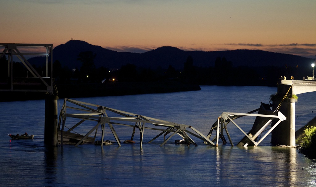 A boat cruises past the scene of a bridge collapse on Interstate 5 on May 23, 2013 near Mt. Vernon, Washington. 1-5 connects Seattle, Washington to Vancouver, B.C., Canada.