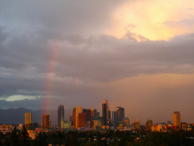 A rainbow, the result of scattered rains, crosses the Los Angeles sky.