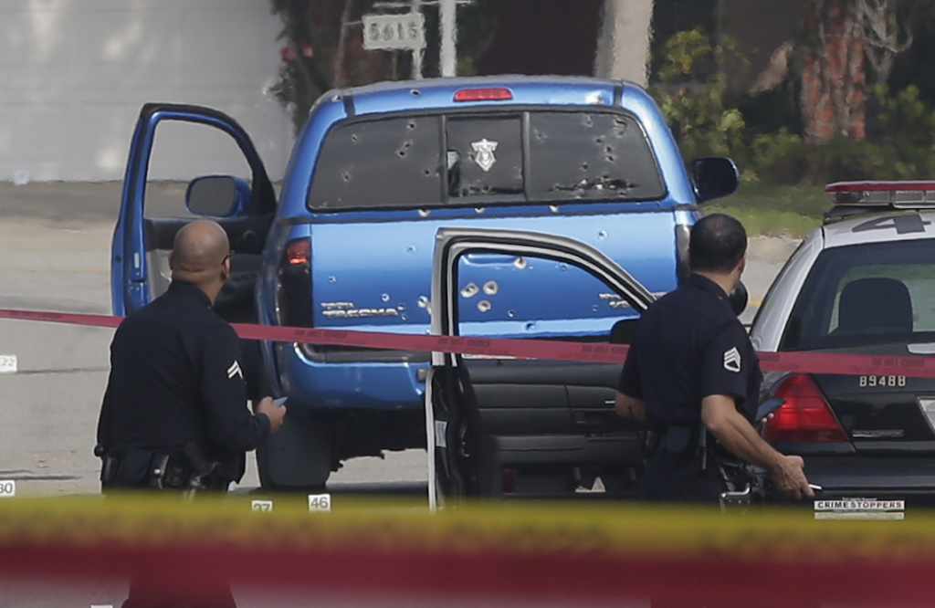 In this Feb. 7, 2013 file photo, law enforcement officers look over the scene of the officer-involved shooting in Torrance, Calif.