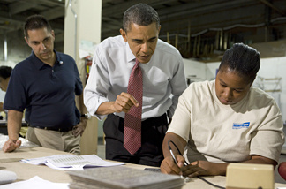 U.S. President Barack Obama (C) speaks with employee Elaine Hart (R) as he tours Gelberg Signs with company Principal Luc Brami during a visit to highlight the administration's initiatives to create jobs August 6, 2010 in Washington, DC.