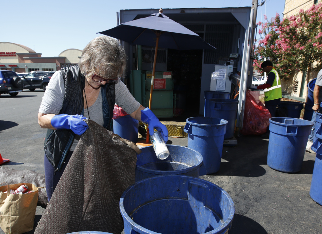 In this photo taken Tuesday, July 5, 2016 Claudette Cole places a plastic bottle into a plastic container at a recycling center in Sacramento, Calif. More than 450 recycling centers statewide have closed in the last year, stripping millions of consumers of easy access to recycling services.