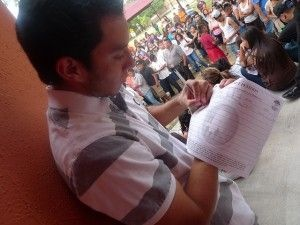 A young man signs a petition during a deferred action informational event in Houston, Texas, June 20, 2010