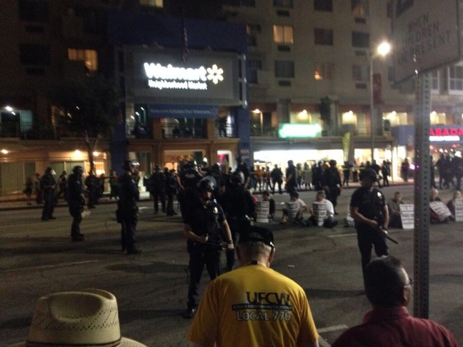 Street sitters drawing cheers, making traffic, at a protest outside new Walmart in Chinatown.