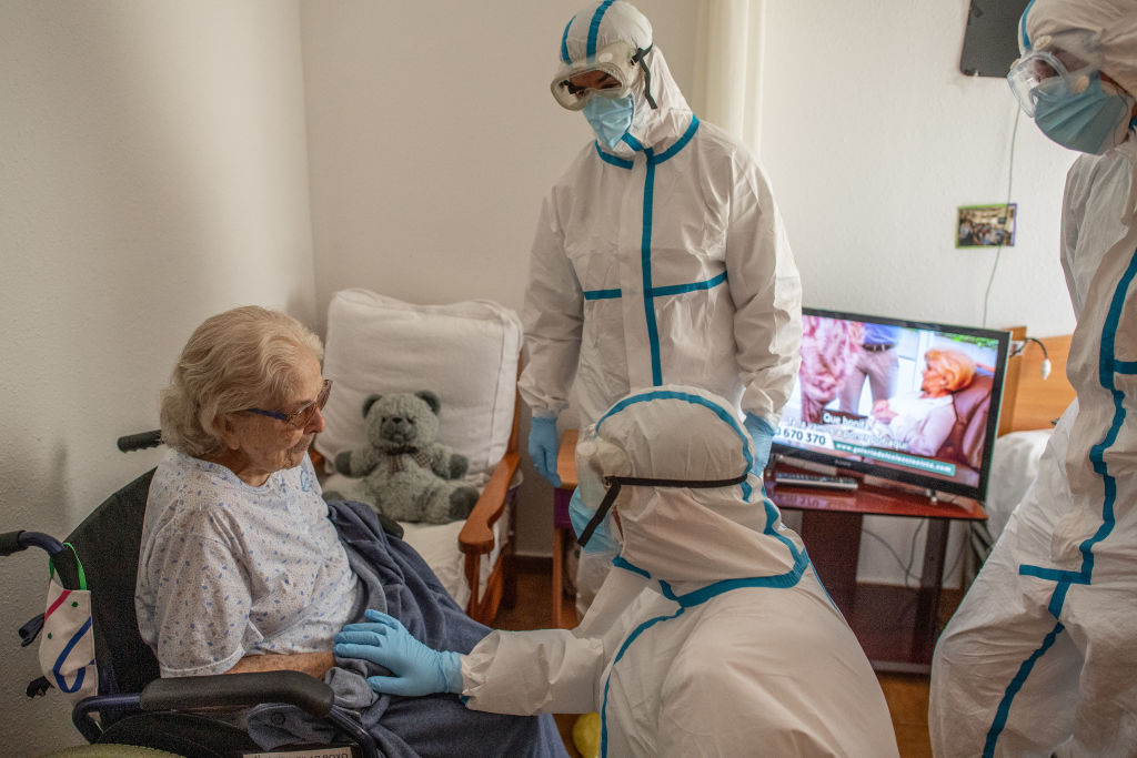 Primary health care nurse Jose Dominguez and physician Joan Maria Farré both in personal protective equipment (PPE) speak with Pilar Boxo who is in quarantine after being tested positive of COVID-19 during a monitoring visit to COVID19 patients at Yayo Toni on May 21, 2020 in Pallejà, Spain.