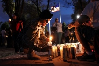 U.S. Army Pfc. Jose Medina, 20, lights a candle during a vigil protesting Arizona's new immigration law outside the Arizona State Capitol building in Phoenix, Arizona. Medina said he came to to the United States from Mexico illegally with his family at age 2 and, along with his parents, was later naturalized as an American citizen.