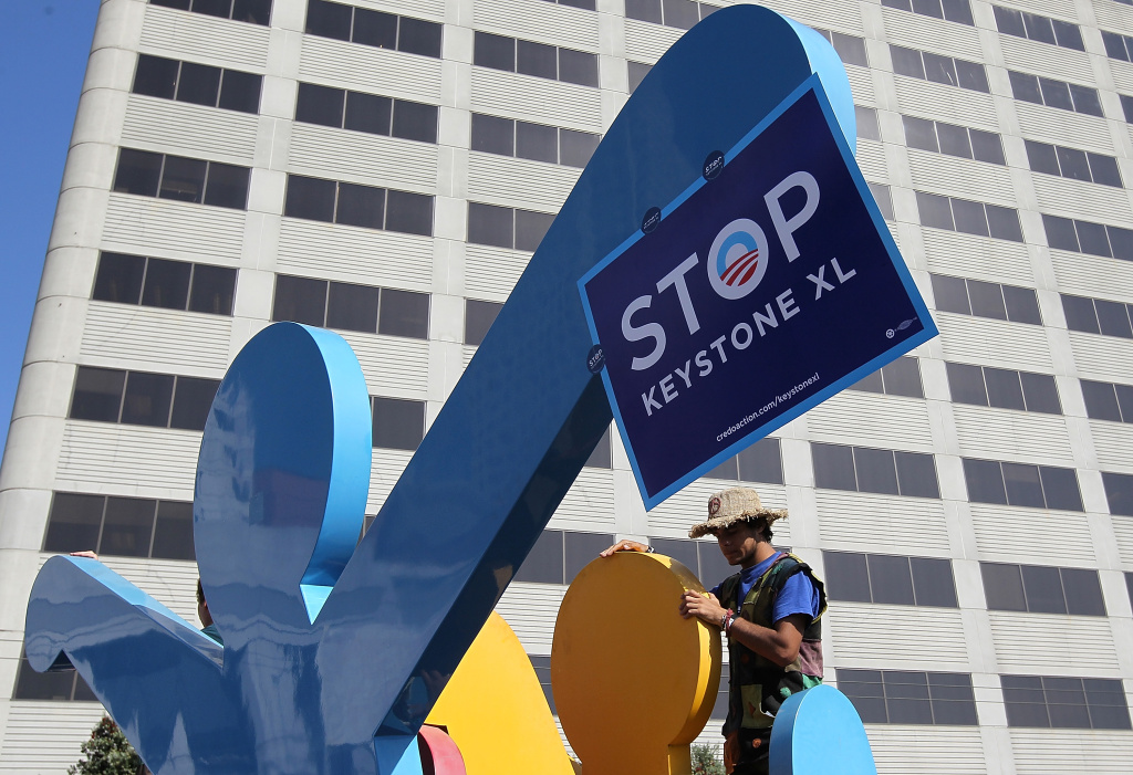 A protestor against the construction of the Keystone XL oil pipeline climbs on a Keith Haring sculpture as he demonstrates outside of the W Hotel where U.S. President Barack Obama was holding a fundraiser on October 25, 2011 in San Francisco, California.