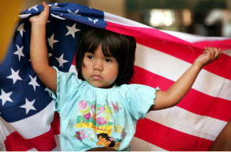 Ana Sari, 3, sits on her father's shoulders as they demonstrate outside the building that houses immigration court along with family and friends of IFCO System employees as they await word on the deportation hearings July 31, 2006 in Chicago, Illinois.