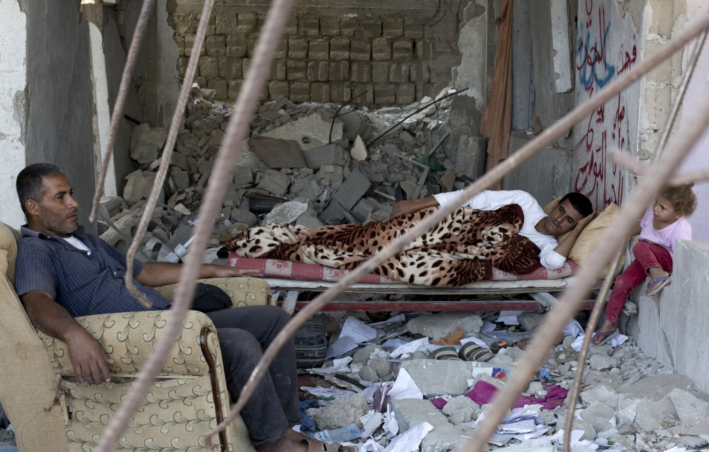 A Palestinian family rests on July 2, 2015, in the rubble of a building that was destroyed during the 50-day war between Israel and Hamas' militants in the summer of 2014, in the al-Shejaeiya neighbourhood, east of Gaza City. AFP PHOTO/MOHAMMED ABED        (Photo credit should read MOHAMMED ABED/AFP/Getty Images)