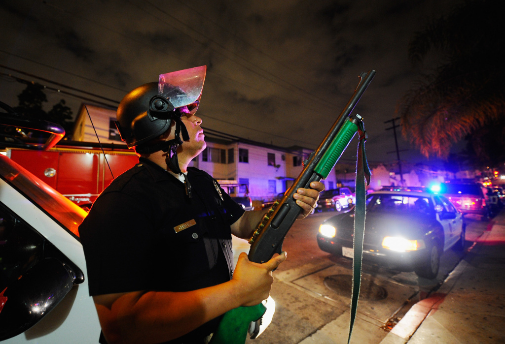A Los Angeles Police officer holds his firearm during demonstrations near the shooting site of Manuel Jamines on September 8, 2010 in Los Angeles. Protesters demonstrated after the shooting of Jamines, a Guatemalan immigrant, by LAPD officers.